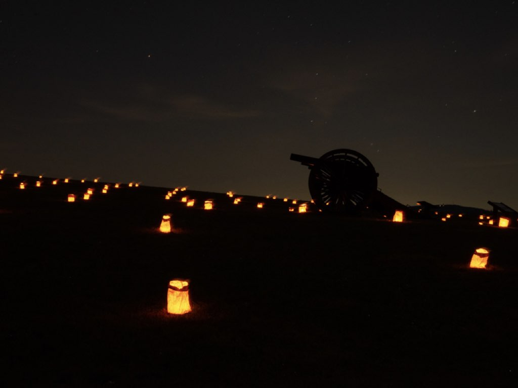 In the night, a cannon stands oustide with lit candles arranged over the ground