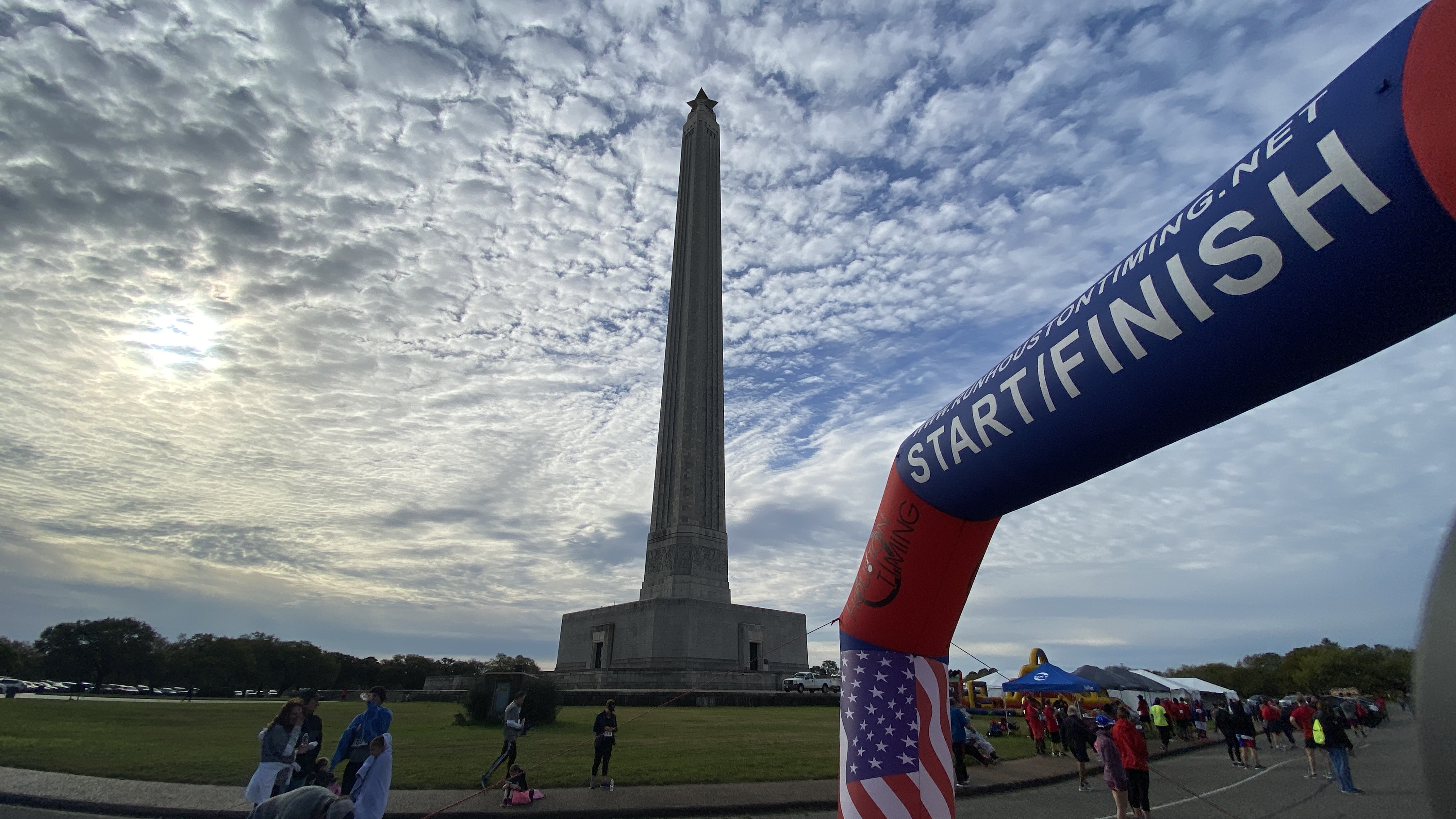 A finish line stands over a road, with the tall San Jacinto Monument backed by fluffy clouds in the background, with pop-up tents and people standing and moving along the road.