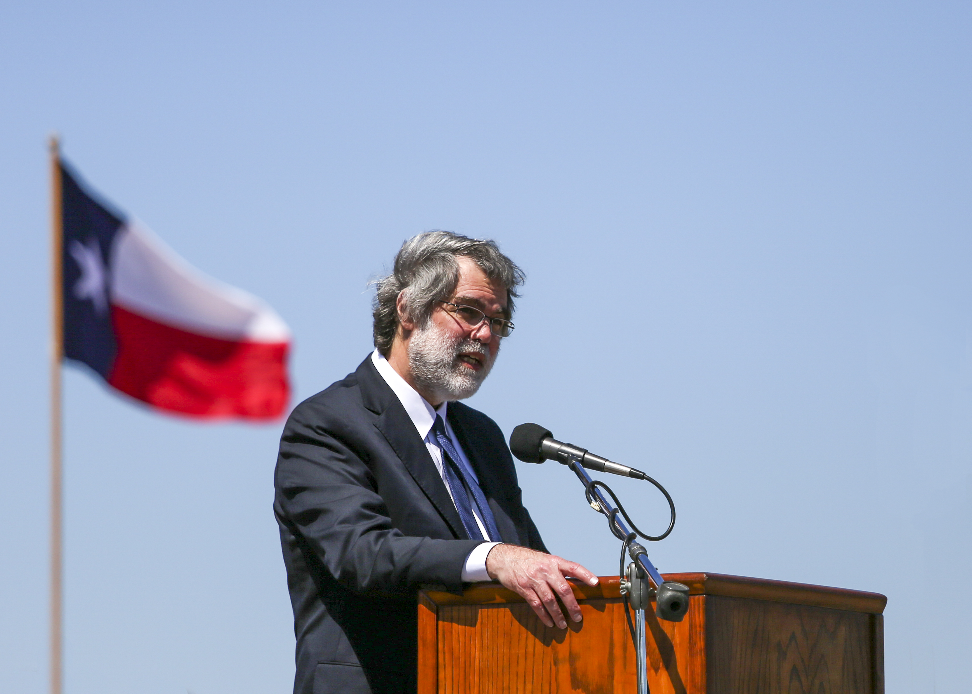 A man wearing a suit stands at a podium outside, with a Texas flag behind him.
